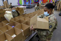 Texas National Guard soldiers Spc. Esmeralda Zuniga, left, and Spc. Samantha McClasky, right, load boxes with various dairy products such as milk, cheese and butter, at the Houston Food Bank Wednesday, Oct. 14, 2020, in Houston. When the pandemic hit last March, the volunteer count at the food bank dropped 80 percent. The Guard stepped in to fill the gap and has been assisting ever since. (AP Photo/Michael Wyke)