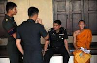 A Thai Buddhist monk sits with soldiers after he was selected as a military recruit - through a lottery system - during a process held at a temple grounds in Bangkok. By law all Thai men who do not volunteer for military service must attend the conscription lottery at least once after they turn 21