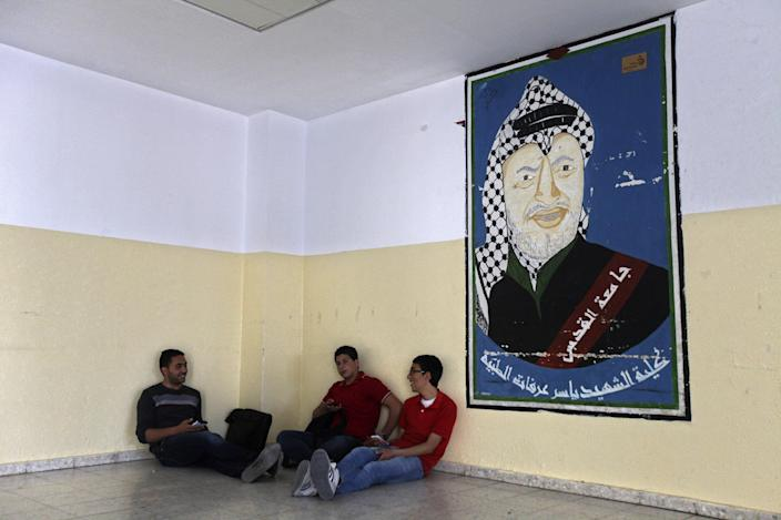 """In this Wednesday, April 9, 2014 photo, Palestinians students sit next to a picture of late Palestinian leader Yasser Arafat at the Al-Quds University in the West Bank village of Abu Dis, near Jerusalem. Dozens of Palestinian doctors who graduated from Al-Quds University, a school that has a foothold in east Jerusalem, are caught in the political battle between Israel and the Palestinians over the city's eastern sector. Israel has refused to recognize the university's graduates -- a move that could amount to acknowledging the Palestinian claims to east Jerusalem as their capital. Arabic on picture reads, """"Faculty of Medicine, martyr, leader Yasser Arafat, Al-Quds University."""" (AP Photo/Majdi Mohammed)"""