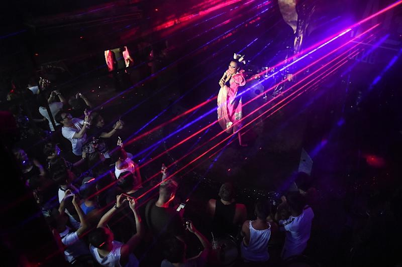 Bathed in a pink spotlight, the cabaret singer at Phuket's 'ZAG' bar lip-syncs the top notes of a popular Mandarin love song, delighting the crowd of gay Chinese tourists who have escaped judgement at home for sexual freedom in Thailand (AFP Photo/LILLIAN SUWANRUMPHA)