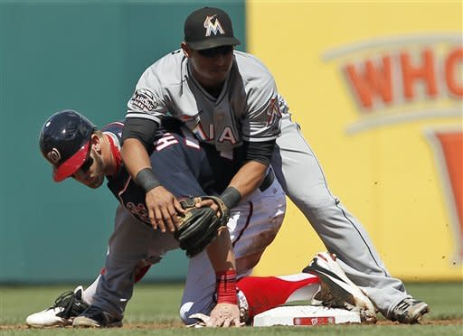 Washington Nationals' Bryce Harper, bottom, is out at second base as he gets tangled up with Miami Marlins second baseman Donovan Solano as Solano turns the double play during the first inning of a baseball game at Nationals Park, Sunday, Sept. 9, 2012, in Washington. (AP Photo/Alex Brandon)