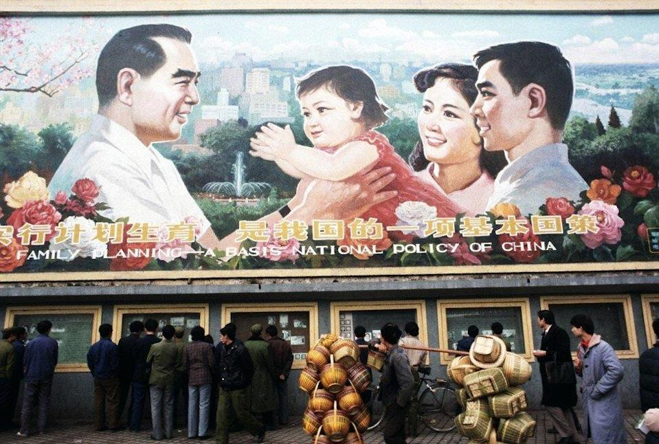 Pedestrians and a man carrying baskets pass by a huge billboard extolling the virtues of China's 'One Child Family' policy. Photo: Getty