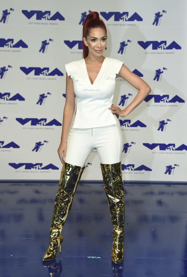 <p>Farrah Abraham wore white jeans with thigh-high gold boots. (Photo: AP) </p>