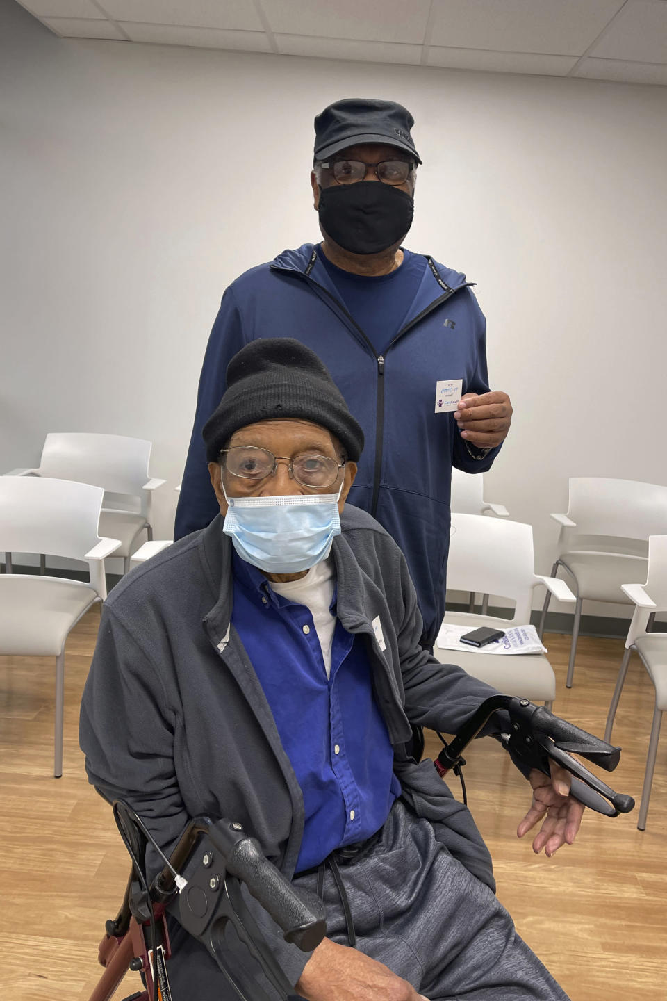 This image provided by CareSouth Medical and Dental, Larry Hamilton, 70, standing, brings his father Leo Hamilton, 96, to CareSouth Medical and Dental on Jan. 22, 2021, in Baton Rouge, La., to receive his COVID-19 vaccine. The CareSouth clinic in Baton Rouge was recruited to join the COVID-19 vaccination campaign after the Louisiana Department of Health used maps and data to locate vulnerable neighborhoods without vaccination sites. (CareSouth Medical and Dental via AP)