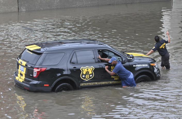 A vehicle is pushed out of flood waters along Interstate 75 near Superior Street in Detroit on Saturday, June 26, 2021. (Max Ortiz/Detroit News via AP)