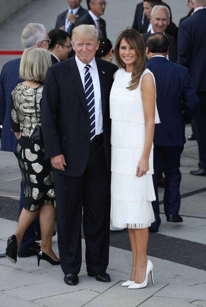 """<p>The first lady wore a <a href=""""http://www.vogue.com/article/melania-trump-michael-kors-christian-louboutin-g20-summit-celebrity-first-lady-style"""" rel=""""nofollow noopener"""" target=""""_blank"""" data-ylk=""""slk:high-necked white flapper-inspired dress by Michael Kors"""" class=""""link rapid-noclick-resp"""">high-necked white flapper-inspired dress by Michael Kors</a> to a concert and dinner for world leaders at the G20 Summit in Hamburg.</p>"""