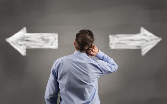 A man in a blue button-down shirt, with his back turned, looking at white arrows on a gray wall pointing left and right