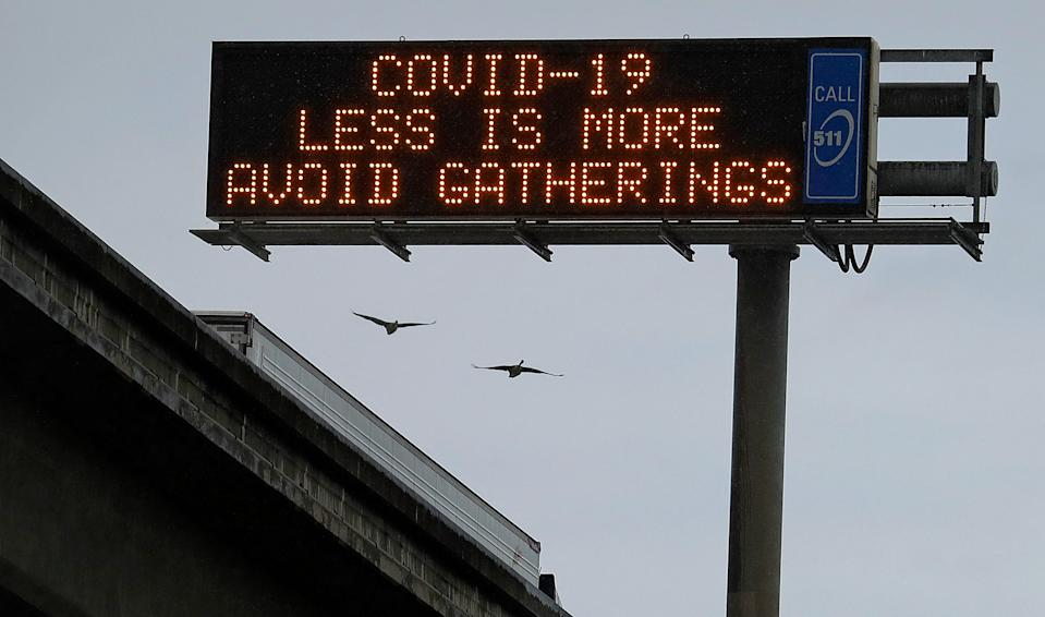 A COVID-19 warning sign is displayed along westbound Interstate-880, Saturday, March 14, 2020, in San Leandro, Calif. The California Department of Transportation is displaying public health messages concerning the coronavirus on the state's more than 700 electric signs. (AP Photo/Ben Margot)
