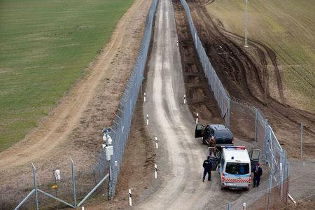 A Hungarian police and soldiers patrol the Hungary-Serbia border, which was recently fortified by a second fence, near the village of Gara