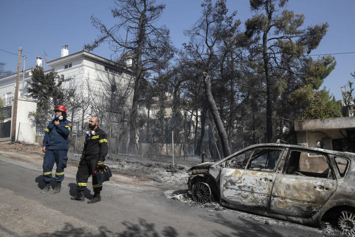 Firefighters look out a burnt car following a forest fire at Dionysos northern suburb of Athens, on Tuesday, July 27, 2021. Greek authorities have evacuated several areas north of Athens as a wildfire swept through a hillside forest and threatened homes despite a large operation mounted by firefighters. (AP Photo/Yorgos Karahalis)