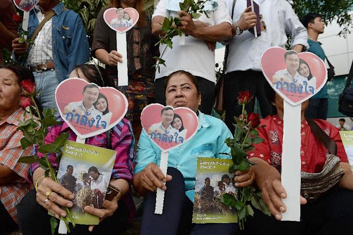 Supporters hold flowers and heart-shaped cut-outs carrying pictures of deposed former Thai premiers Yingluck Shinawatra (R) and her brother Thaksin, outside the supreme court in Bangkok, on January 15, 2016 (AFP Photo/Christophe Archambault)