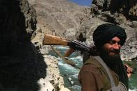 FILE - In this Oct. 8, 1996 file photo, a Taliban soldier patrols the entrance to the Panjshir Valley, north of Kabul. In August 2021, the last remnants of Afghanistan's shattered security forces have vowed to resist the Taliban in the remote Panjshir Valley north of Kabul, that has defied conquerors before. Under the leadership of late charismatic guerrilla fighter Ahmad Shah Massoud, fighters in the Panjshir Valley held off the Soviets in the 1980s and the Taliban a decade later. Any attempt to re-enact his exploits appears likely to fail, posing little threat to the country's new Taliban rulers.. (AP Photo/John Moore, File)