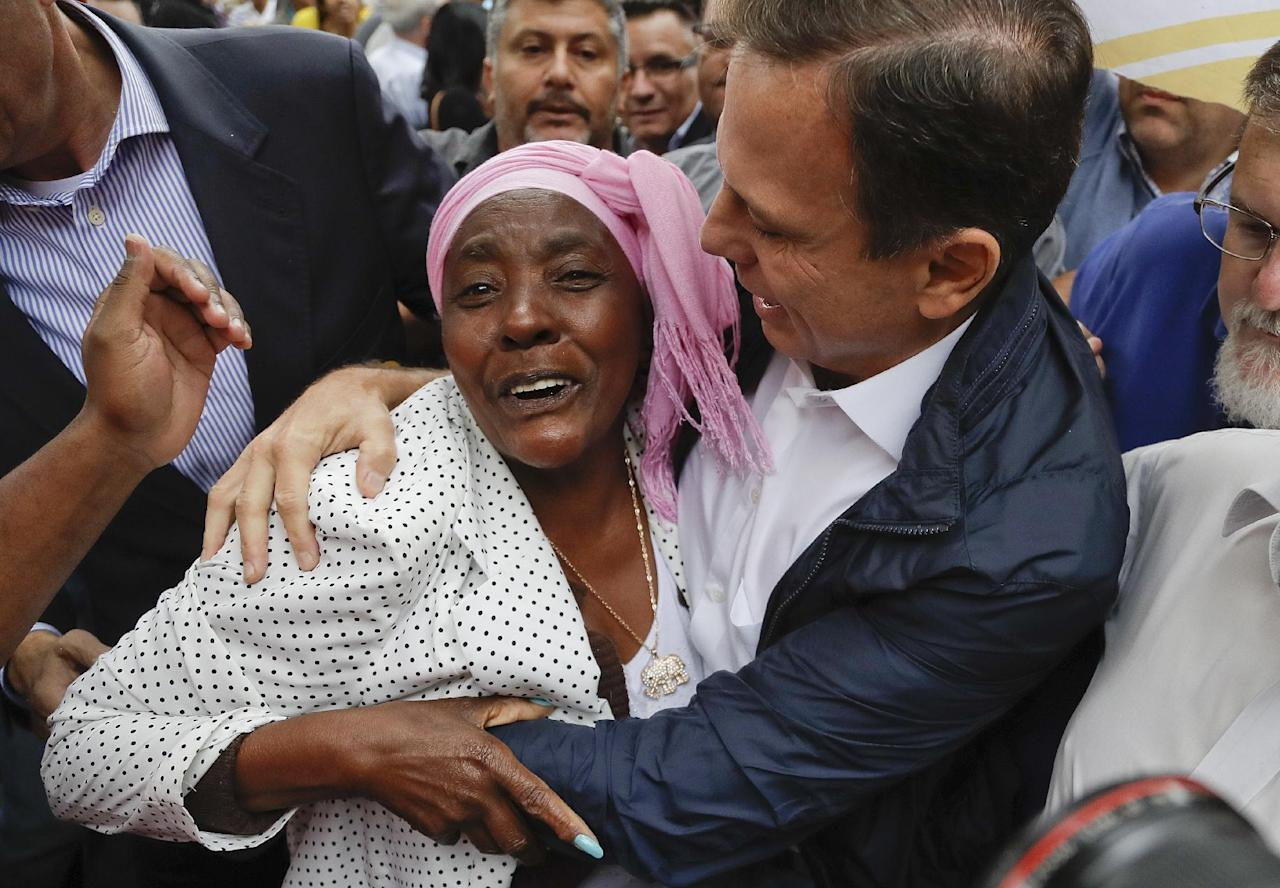 Joao Doria, mayoral candidate of the Brazilian Social Democracy Party, right, embraces a supporter as he campaigns in Sao Paulo, Brazil, Friday, Sept. 30, 2016. The first round of nationwide mayoral elections are scheduled for Sunday, Oct. 2. (AP Photo/Andre Penner)