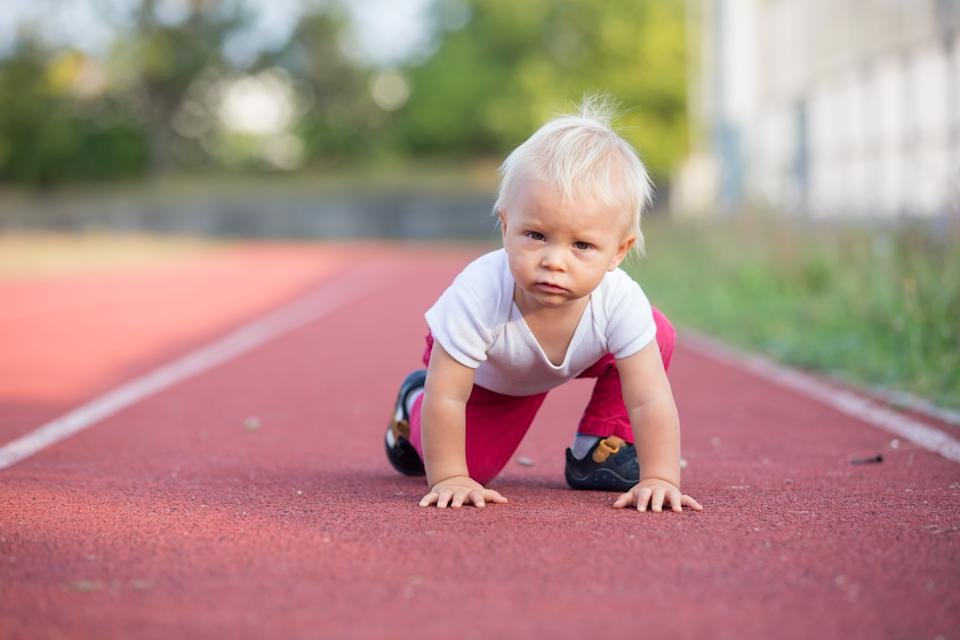 Little toddler baby boy, playing on stadium, prepare for run