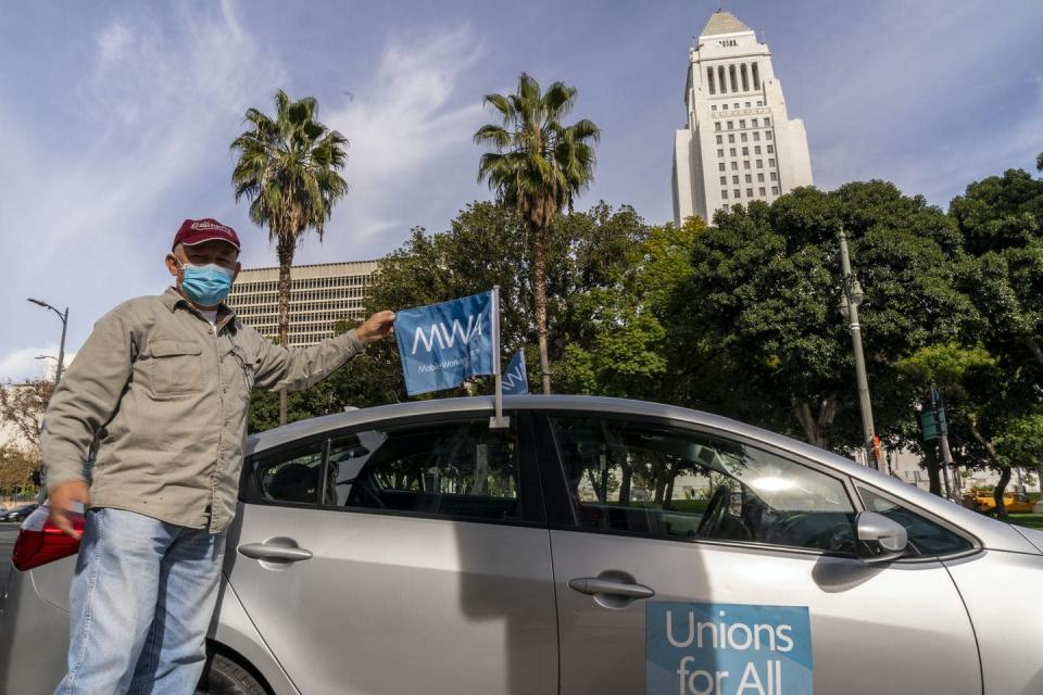 A Uber driver wearing a mask stands beside his car that has a Unions For All banner on the passenger door.