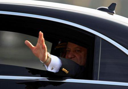 Pakistan's Prime Minister Nawaz Sharif waves from a vehicle as he arrives to attend the Pakistan Day military parade in Islamabad, Pakistan