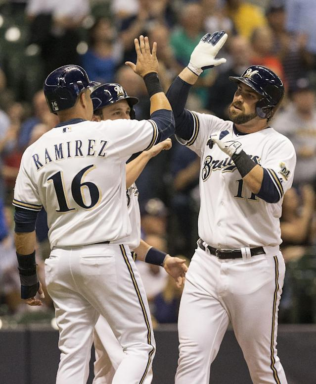 Milwaukee Brewers' Sean Halton, right, celebrates with teammates Aramis Ramirez (16) and Jonathan Lucroy at home plate after connecting for a grand slam off Chicago Cubs' Chris Rusin during the first inning of a baseball game on Wednesday, Sept. 18, 2013, in Milwaukee. (AP Photo/Tom Lynn)