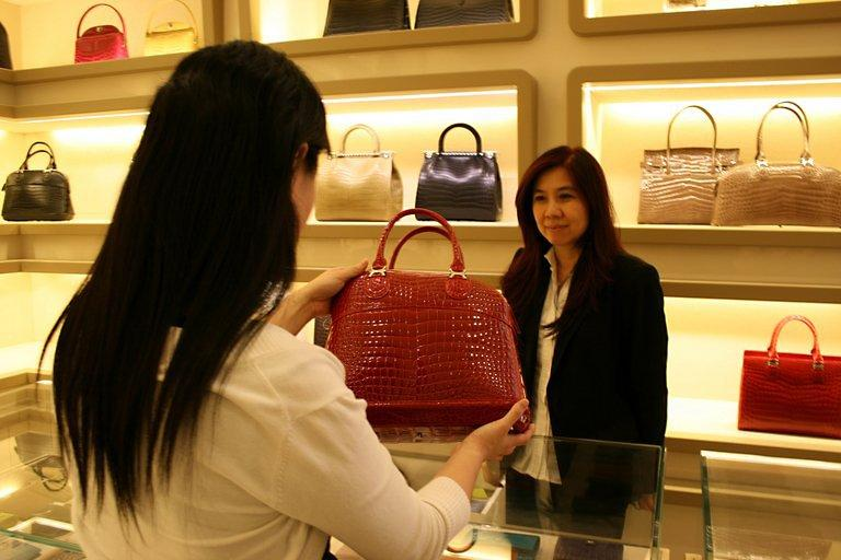 A customer looking at a crocodile leather handbag at a Kwanpen boutique in Singapore in March 2010. In a luxury industry dominated by famous European brands, a Singapore company is making inroads with an exclusive line of colourful handbags made from crocodile skin