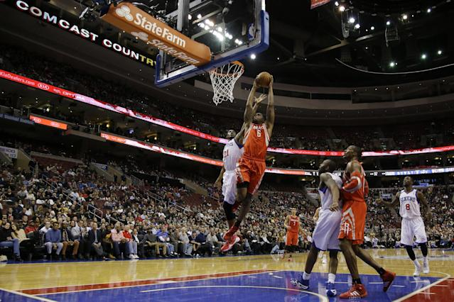Houston Rockets' Terrence Jones (6) goes up for a dunk as Philadelphia 76ers' Thaddeus Young (21) defends during the first half of an NBA basketball game, Wednesday, Nov. 13, 2013, in Philadelphia. (AP Photo/Matt Slocum)