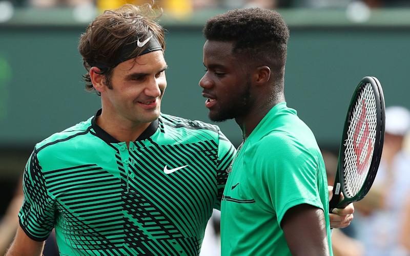 Roger Federer consolesFrances Tiafoe at the net - Getty Images North America