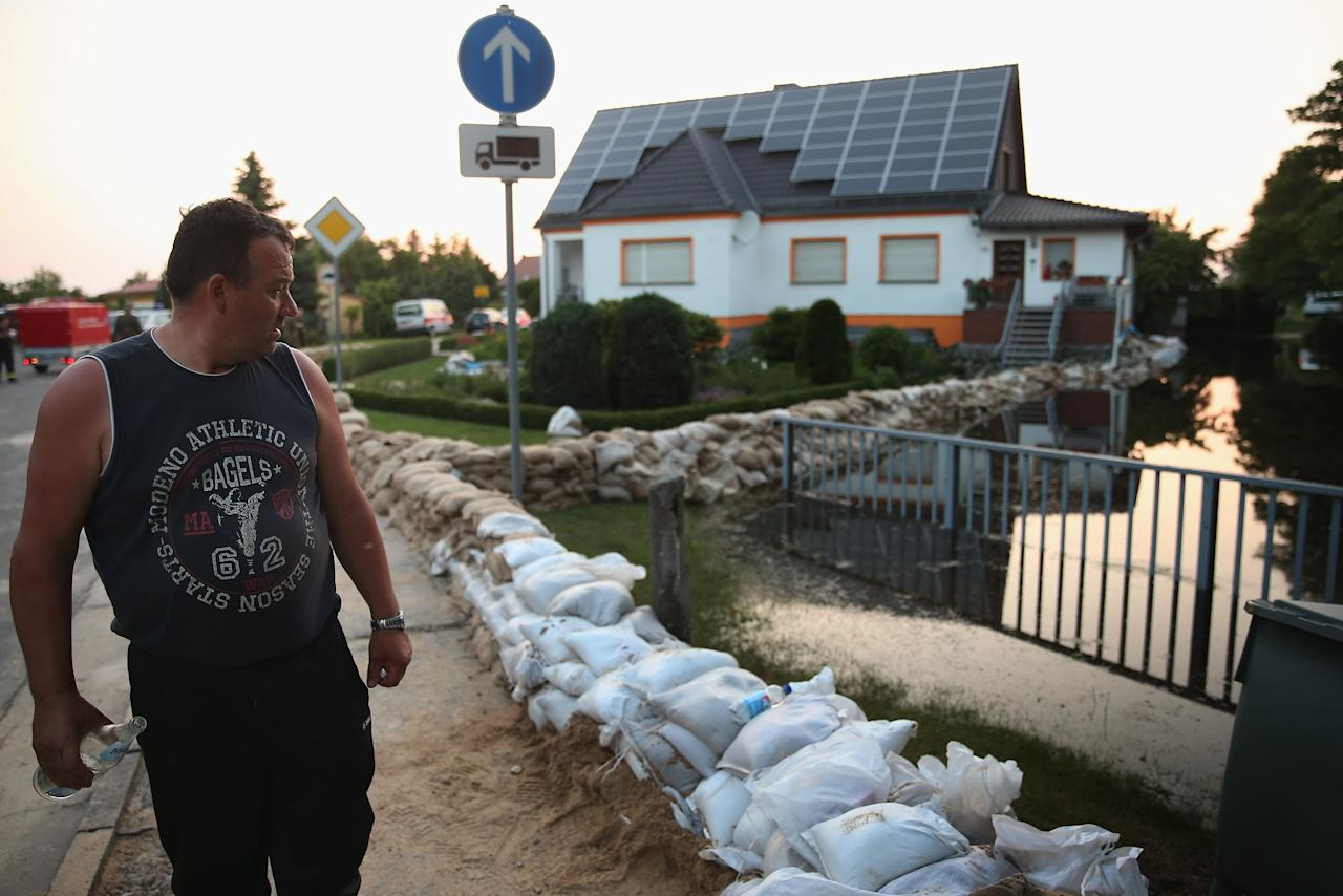 WUST, GERMANY - JUNE 11:  A local resident looks at water encroaching upon his home as sandbags stacked by volunteers stand in rows to protect it from the spreading floodwaters of the Elbe river on June 11, 2013 in Wust, Germany. About a half dozen villages  in Stendal county and large tracts of farmland are inundated following the collapse of a dyke at nearby Fischbeck two days ago. Floods have ravaged portions of southern and eastern Germany in the last week, leaving at least seven people dead and forcing tens of thousands to evacuate their homes.  (Photo by Sean Gallup/Getty Images)