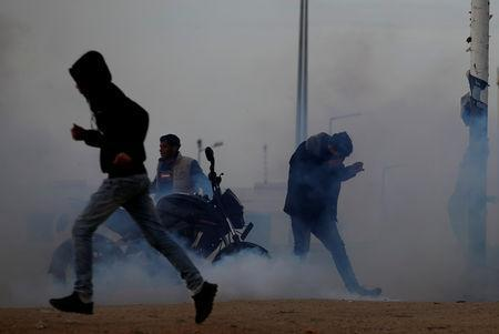 Palestinians react to tear gas fired by Israeli troops during a protest at the Israeli-Gaza border fence, east of Gaza City March 29, 2019. REUTERS/Mohammed Salem