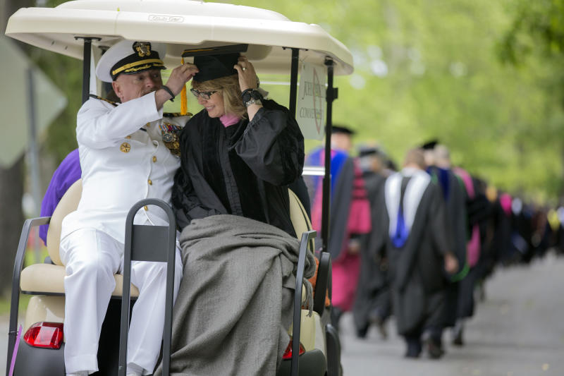 Former U.S. Rep. Gabrielle Giffords leans forward as her husband, retired space shuttle Commander Mark Kelly, adjusts her mortarboard as they ride in the procession for the 153rd Commencement at Bard College, Saturday, May 25, 2013, in Annandale-on-Hudson, N.Y. They delivered the commencement address, and Giffords received an honorary degree. (AP Photo/Philip Kamrass)