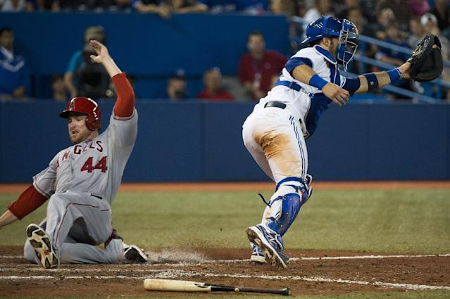 Los Angeles Angels first baseman Mark Trumbo, left, slides safely past Toronto Blue Jays catcher J.P. Arencibia at home plate during the eighth inning of a baseball game in Toronto on Tuesday, Sept. 10, 2013. (AP Photo/The Canadian Press, Nathan Denette)