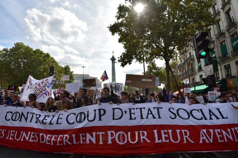 """Demonstrators hold a banner reading """"against the social coup d'etat"""" during a protest over the President Emmanuel Macron's labour reforms"""