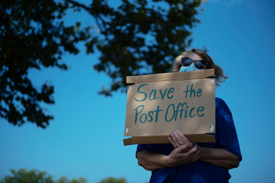 Activist Rebecca Slisher, of Groveport, holds a sign while rallying with others during a Save the Post Office Rally on Saturday, August 22, 2020 in Whitehall, Ohio.