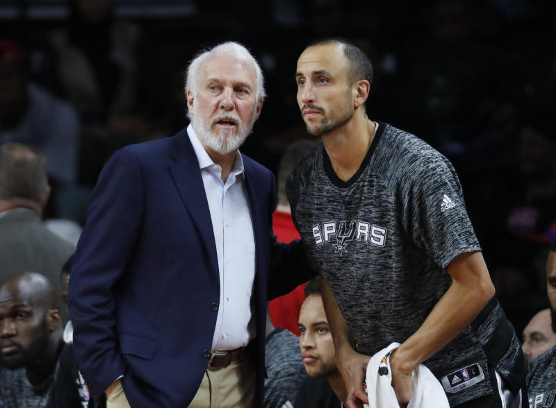 San Antonio Spurs head coach Gregg Popovich talks with San Antonio Spurs guard Manu Ginobili (20) against the Detroit Pistons in the first half of a preseason NBA basketball game in Auburn Hills, Mich., Monday, Oct. 10, 2016. (AP Photo/Paul Sancya)