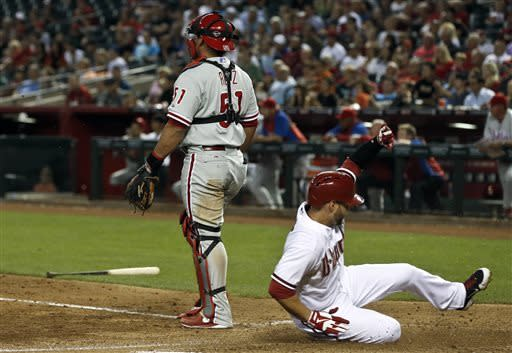 Arizona Diamondbacks' Cody Ross, right, slides in to score a run as Philadelphia Phillies' Carlos Ruiz watches the infield action at first base during the sixth inning of a baseball game on Thursday, May 9, 2013, in Phoenix. (AP Photo/Ross D. Franklin)