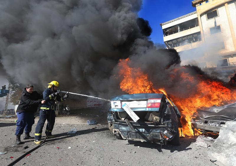 Lebanese firefighters extinguish a burned car at the site of an explosion, in the suburb of Beir Hassan, Beirut, Lebanon, Wednesday Feb. 19, 2014. A blast in a Shiite district in southern Beirut killed at several people on Wednesday, security officials said — the latest apparent attack linked to the civil war in neighboring Syria that has killed and wounded scores of people over the last few months. (AP Photo/Hussein Malla)