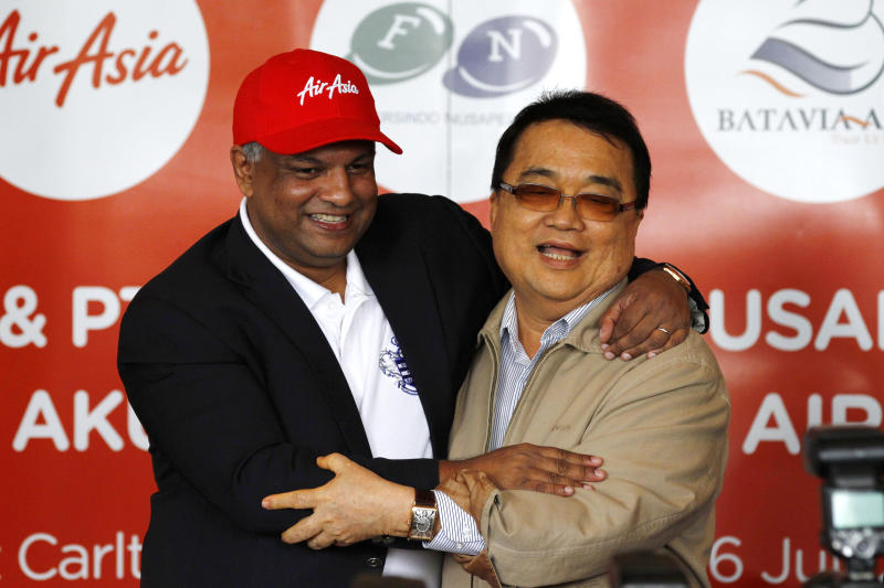 AirAsia Chief Executive Officer Tony Fernandez, left, hugs Batavia Air President Director Yudiawan Tansari during a joint press conference in Jakarta, Indonesia, Thursday, July 26, 2012. Low-cost airline AirAsia said it is buying Indonesian budget carrier Batavia Air to expand in Southeast Asia's biggest economy. (AP Photo/Achmad Ibrahim)