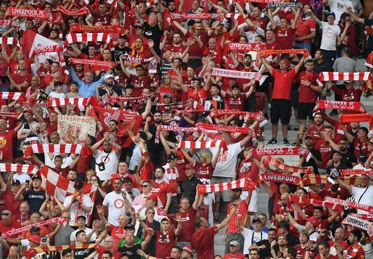 Liverpool football fans hold up their scarves.
