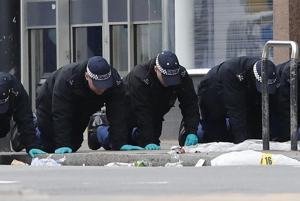 Police officers conducting a finger tip search at the scene following the terror attack in Streatham High Road (Aaron Chown/PA) (PA Wire)