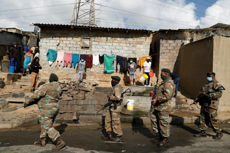 People in the Alexandra township near Johannesburg watch as an army patrol passes by