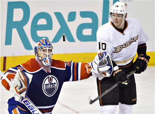 Anaheim Ducks' Corey Perry (10) looks for the rebound as Edmonton Oilers goalie Devan Dubnyk makes the save during the second period of their NHL hockey game in Edmonton, Alberta, Sunday, April 21, 2013. (AP Photo/The Canadian Press, Jason Franson)