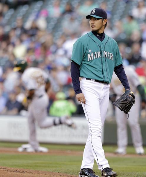 Seattle Mariners starting pitcher Hisashi Iwakuma, right, looks away as Oakland Athletics' Yoenis Cespedes rounds the bases on a home run in the first inning of a baseball game on Friday, June 21, 2013, in Seattle. (AP Photo/Elaine Thompson)