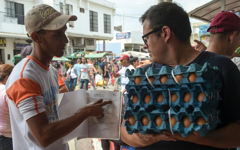 Giovanni Jose Plaza (L), a Venezuelan migrant suffering from AIDS, asks passersby in the border town of Cucuta, Colombia for money to buy medications (AFP Photo/Raul ARBOLEDA)