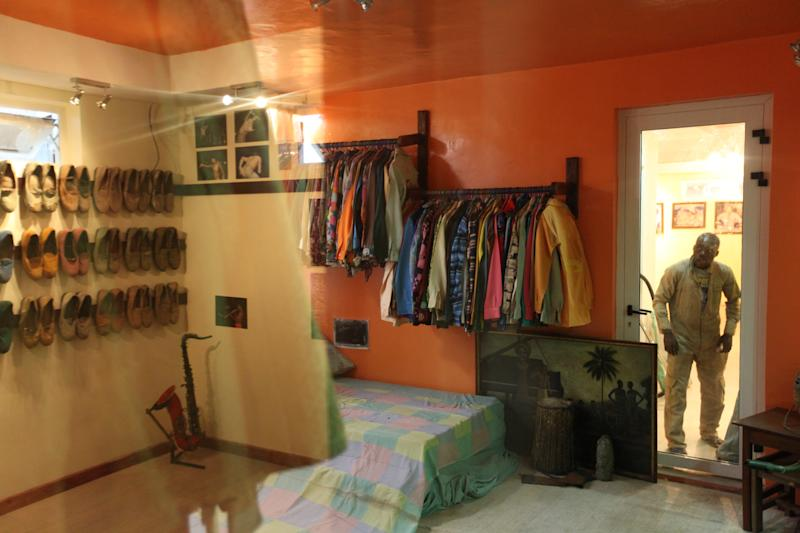 An onlooker peers into the preserved bedroom of singer Fela Anikulapo-Kuti while a reflection of a room containing the musician's shoes and a saxphone can be seen in a reflection in Lagos, Nigeria, on Monday, Oct. 15, 2012. The family of late Afrobeat singer Fela Anikulapo-Kuti celebrated the opening of the Kalakuta Museum on Monday in Lagos in the home the musician once lived in. The opening of the museum comes during Felabration, an annual music festival honoring the singer. (AP Photo/Jon Gambrell)
