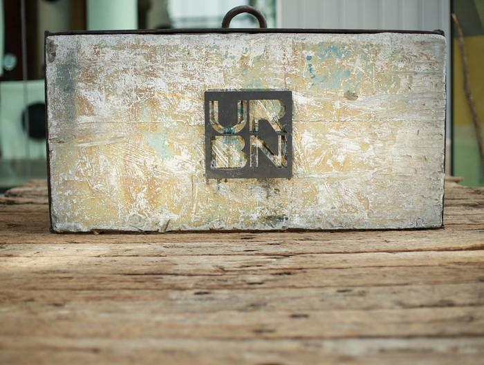 Box with handle and URBN logo on a wood table.