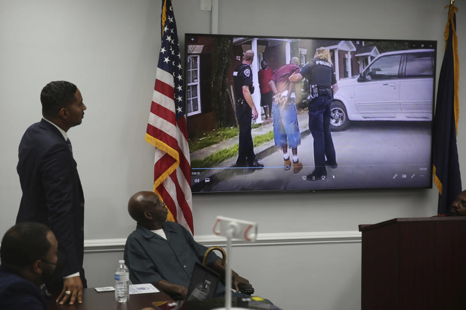 Attorney Justin Bamberg, left and and his client Clarence Gailyard, right, watch police body camera video of an officer stomping Gailyard in the neck as Bamberg holds a news conference on Tuesday, Aug. 3, 2021 in Orangeburg, South Carolina. Orangeburg Public Safety officer David Lance Dukes was fired and charged with a felony after the July 26 incident. (AP Photo/Jeffrey Collins)