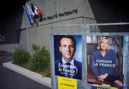 New official posters for the candidates for the 2017 French presidential election, Emmanuel Macron (L), head of the political movement En Marche !, or Onwards !, and Marine Le Pen (R), French National Front (FN) political party leader, are displayed in Fontaines-sur-Saone, near Lyon, France, April 30, 2017. REUTERS/Robert Pratta