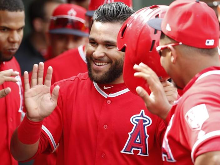 Angels' Jose Rojas high-fives teammates after scoring on a double by Wilfredo Tovar.