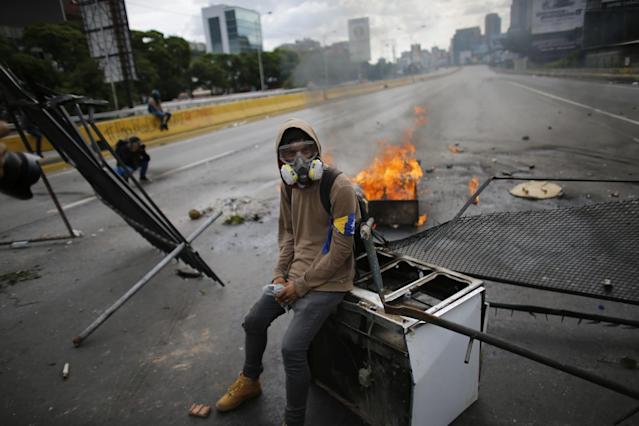 <p>A demonstrator sits on a discarded stove at a barricade, during a national sit-in against President Nicolas Maduro, in Caracas, Venezuela, Monday, May 15, 2017. (AP Photo/Ariana Cubillos) </p>