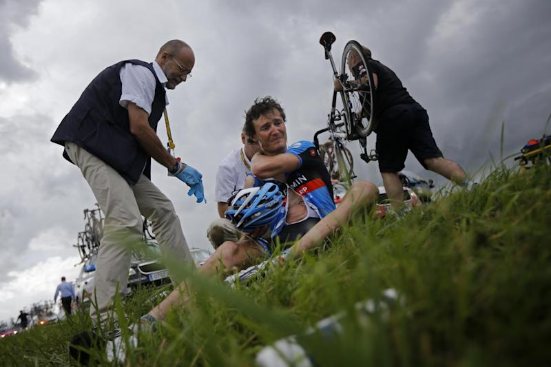 A doctor tends to Johan van Summeren of Belgium after a crash in the pack at some 20 kilometers from he finish line during the sixth stage of the Tour de France cycling race over 207.5 kilometers (129 miles) with start in Epernay and finish in Metz, France, Friday July 6, 2012. (AP Photo/Laurent Cipriani)