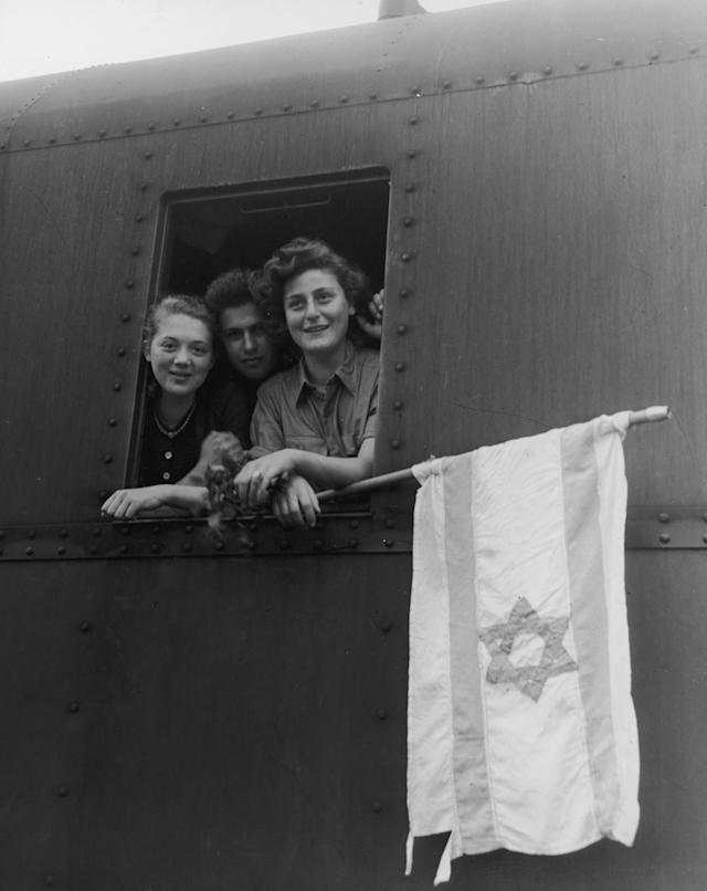 5th June 1945: Jewish teenagers from Poland, Latvia and Hungary look out the window of a train while holding a flag bearing the Star of David, en route to Palestine after being released from the Buchenwald Concentration Camp. (Photo by US Army/Getty Images)