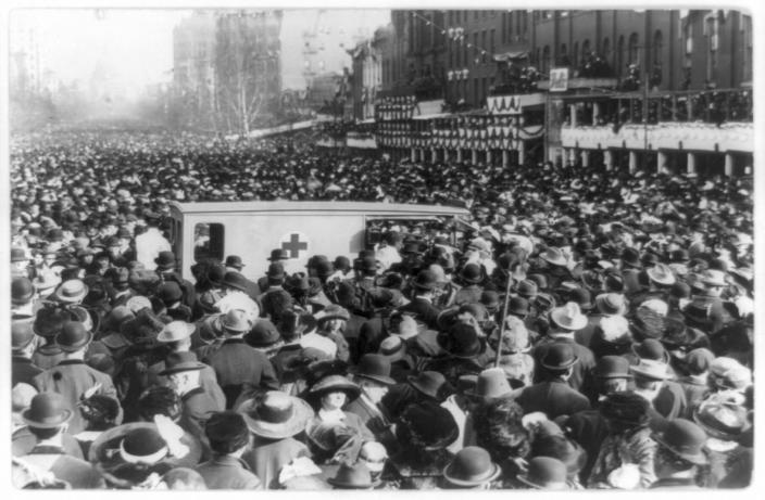 In this photo provided by the Library of Congress, taken in 1913, a crowd gathers around a Red Cross ambulance during the women's suffrage procession in Washington. Thousands of women take to the streets of Washington, demanding a greater voice for women in American political life as a new president takes power. This will happen on Saturday, Jan. 21, 2017, one day after the inauguration of Donald Trump. This DID happen more than 100 years ago, one day before the inauguration of Woodrow Wilson. (Library of Congress via AP)