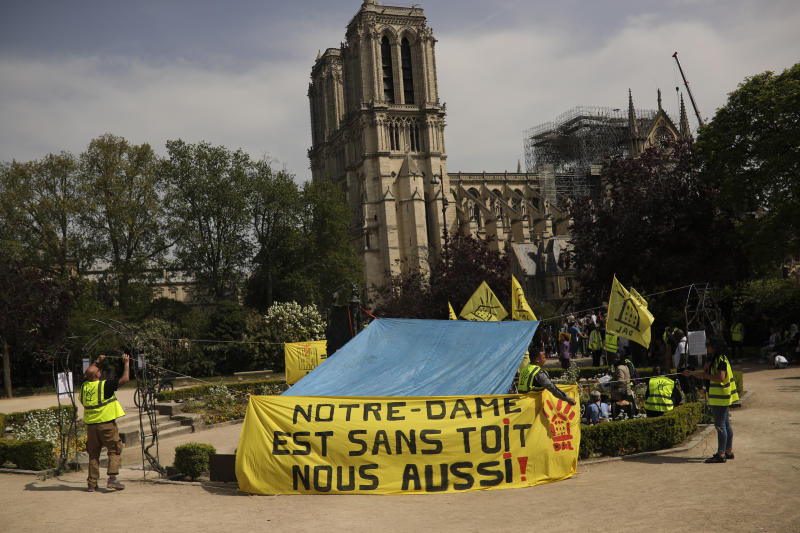 """People fix a banner that reads in French: """"Notre-Dame is roofless, we too!"""" during a protest in front of the Notre Dame cathedral in Paris, Monday, April 22, 2019. (AP Photo/Francisco Seco)"""